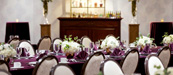 Table set with purple napkins & tablecloth, white chairs, flowers, and a bar in the background