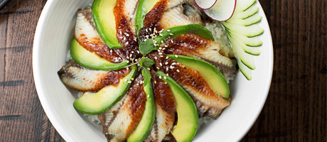 Fish and avocado arranged in a pinwheel on a white plate