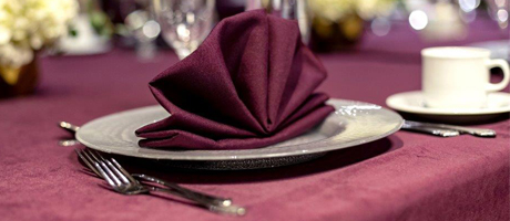 Table set with white dishes, silverware, and maroon napkins and tablecloth