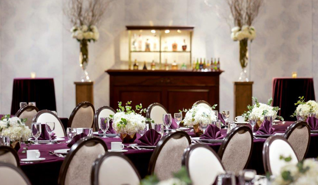 Dining table set with purple tablecloth & napkins, white chairs, flowers, and a bar in the background