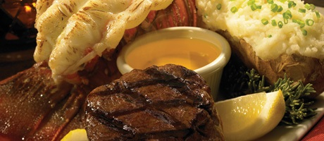 Lobster, steak, and baked potato with a ramakin of melted butter